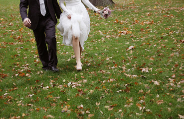 Bride and groom running on grass