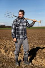 Landwirt mit Mistgabel auf seinem Feld