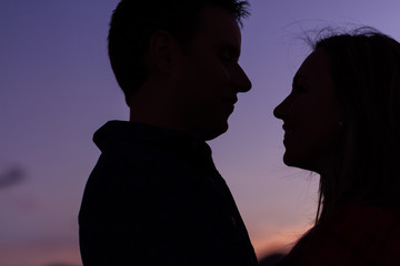Closeup of couple looking at each other at sunset