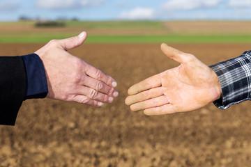 Handschlag zwischen Geschäftsmann und Landwirt vor Acker