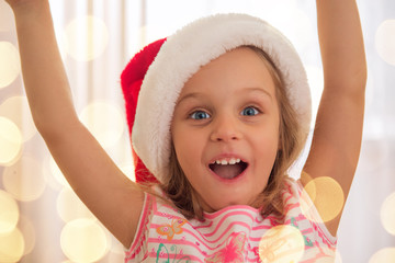 Cute little girl in Santa's hat enjoying at home. Holiday lights