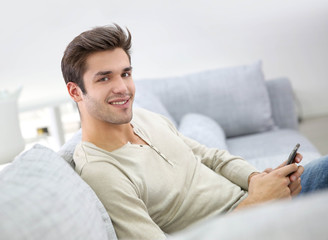 Smiling handsome man using smartphone sit in couch