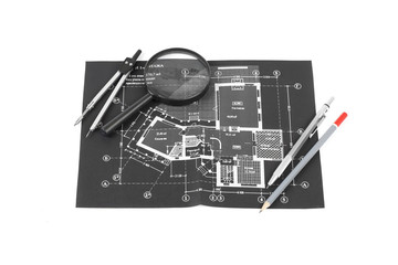 A compass, magnifier and a pencils over a construction drawing o