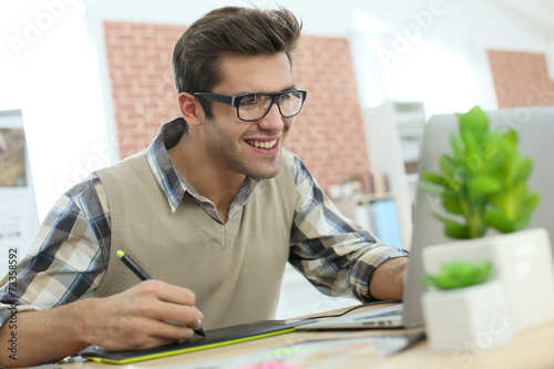 canvas print picture Young man in office using graphic tablet
