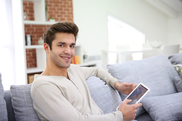 Man sitting in couch and websurfing on internet