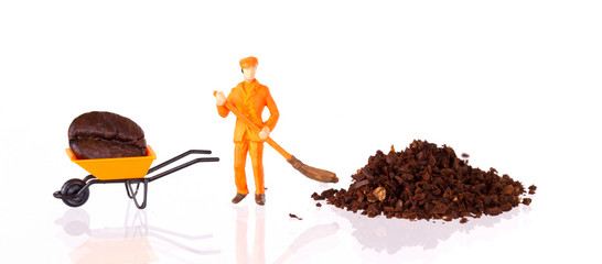 Miniature worker working on a coffee bean