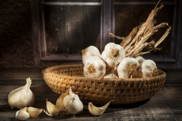 Organic garlic in a straw basket in a dark background