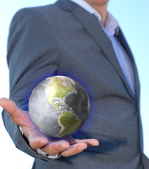Young businessman holding in his hand a glowing earth globe