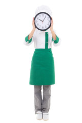 woman chef in uniform holding office clock behind her face - ful