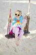 mädchen sitzt auf schaukel am strand