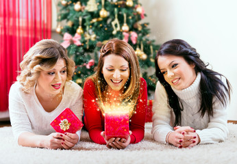 Three beautiful young women opening a magical Christmas present