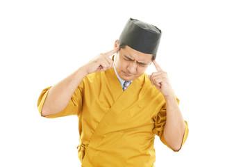 疲れた表情の寿司職人