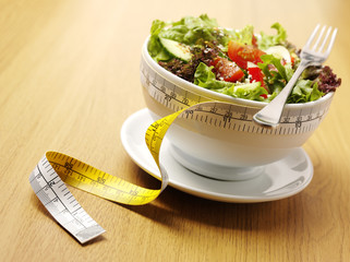 A bowl of mixed salad with a tape measure for healthy eating
