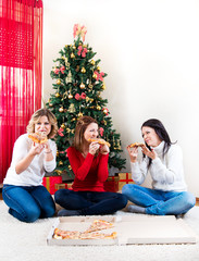 Three young woman eating pizza in front of Christmas tree