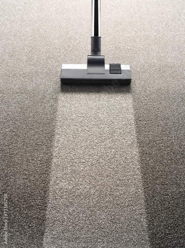 Vacuum cleaner on a carpet with an extra clean strip
