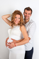 Happy Pregnant Couple dressed in white on white background