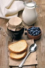 Bread, blueberry jam and milk on wooden table