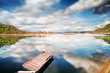 canvas print picture - Completely calm lake with small jetty and reflections