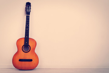 Guitar on the floor on wall background