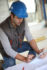 Builder with blue security helmet using tablet
