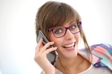 Cheerful girl with eyeglasses talking on phone