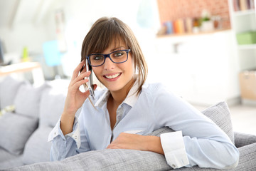 Young woman at home talking on mobile phone