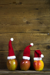 Weihnachtskarte: Holz Hintergrund mit Äpfel und Nikolausmützen