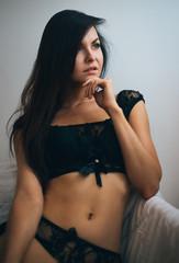 beautiful brunette poses in black underwear