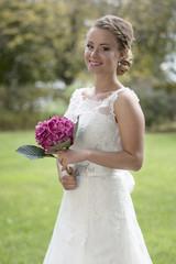 Braut mit Blumen im Garten