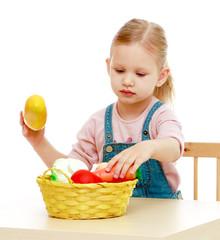 Little girl lying disassembled in a fruit basket.