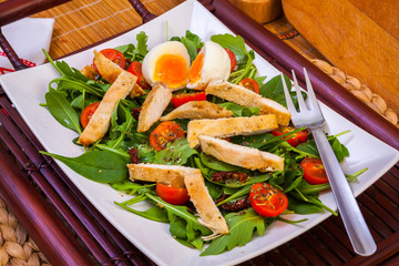 Chicken and egg with vegetables in plate, and fork
