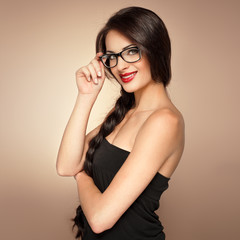 Elegant woman in black dress with naked shoulders in specs