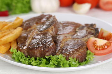 Steaks vom Schwein Fleisch Gericht mit Pommes, Gemüse und Salat