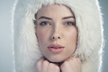 Young woman wearing a white fur cap
