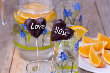 Chocolate Cake pops on the sticks in glass, wooden background