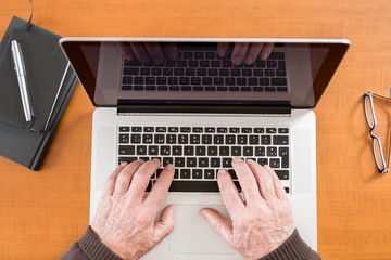 Senior working with Laptop, focus on hands
