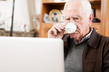 Senior working with Laptop and drinking a coffee