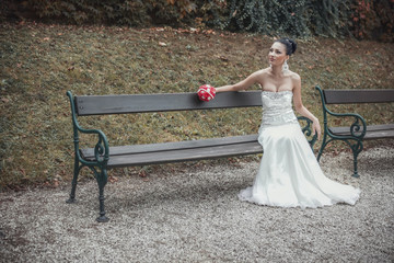 Young beautiful pretty bride sitting on bench