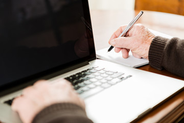 Senior working with Laptop, focus on hand