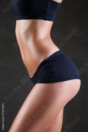 Leinwandbild Motiv Slim woman's body  over dark gray background