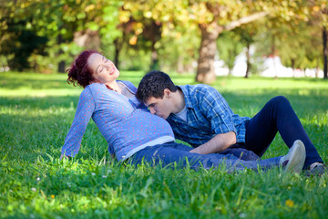 Pregnant couple relaxing in autumn park