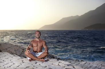 Muscular man meditating in a yoga pose