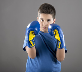 Child boxer takes guard position over gray background.