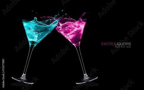 Exotic Liquors. Stemmed cocktail glasses making a toast splashin - 73377987