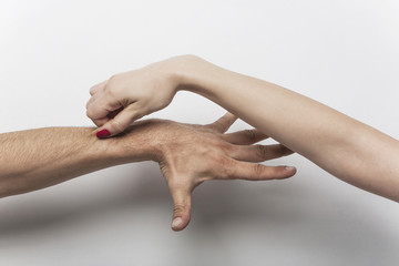 Woman's hand pinching man's arm