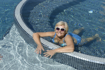 Aged woman is lying prone in blue water of pool.