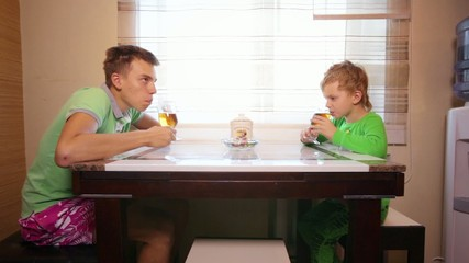 Two boys have breakfast with sweets and tea