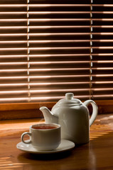 tea cup with teapot against the background of blinds
