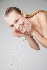 Beautiful woman washing her clean face with water