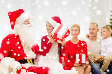 smiling family with santa claus and gifts at home